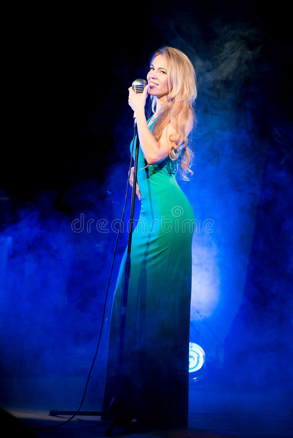 Singer woman singer sings a song with retro microphone on blue smoke background. Concert. Singer woman singer sings a song with retro microphone on blue smoke stock image