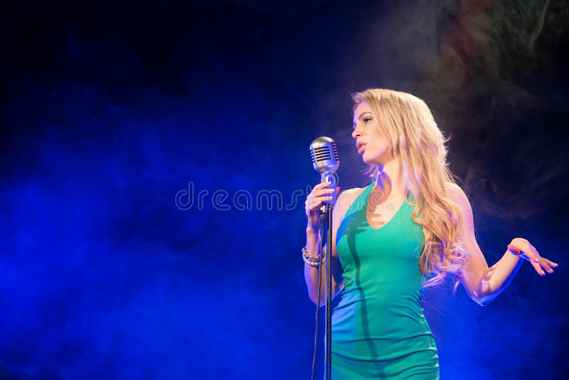 Singer woman singer sings a song with retro microphone on blue smoke background. Concert. Singer woman singer sings a song with retro microphone on blue smoke royalty free stock photos