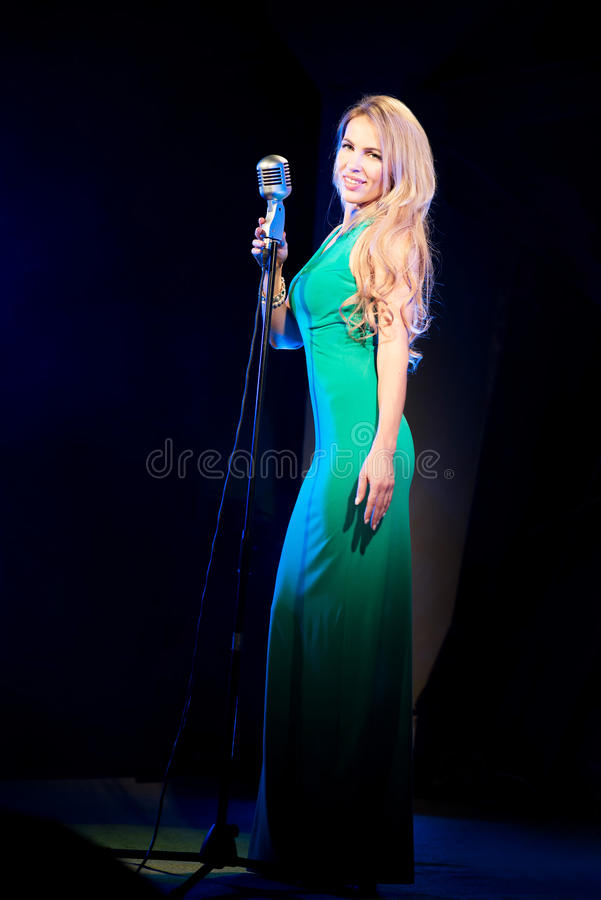 Singer woman singer sings a song with retro microphone on blue smoke background. Concert. Singer woman singer sings a song with retro microphone on blue smoke royalty free stock photo