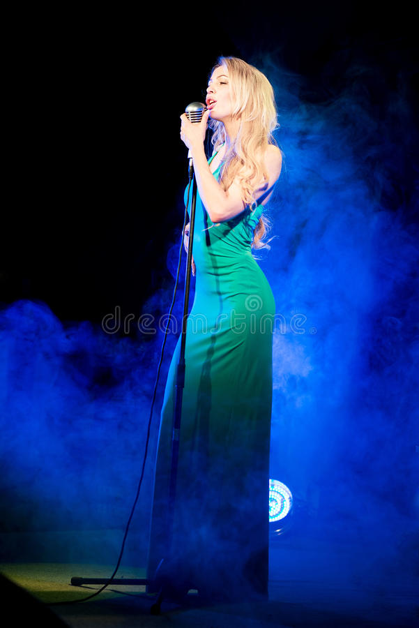 Singer woman singer sings a song with retro microphone on blue smoke background. Concert. Singer woman singer sings a song with retro microphone royalty free stock images