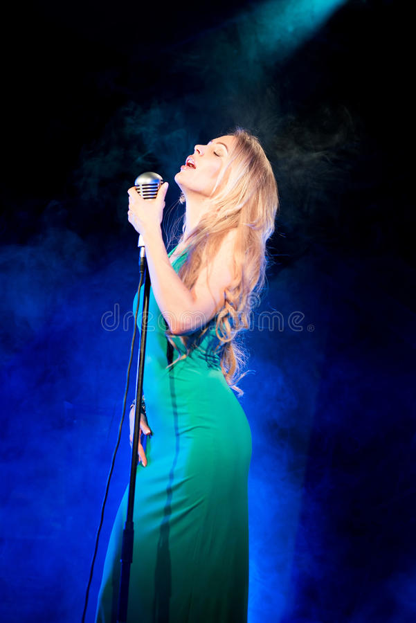 Singer woman singer sings a song with retro microphone on blue smoke background. Concert. Singer woman singer sings a song with retro microphone stock image