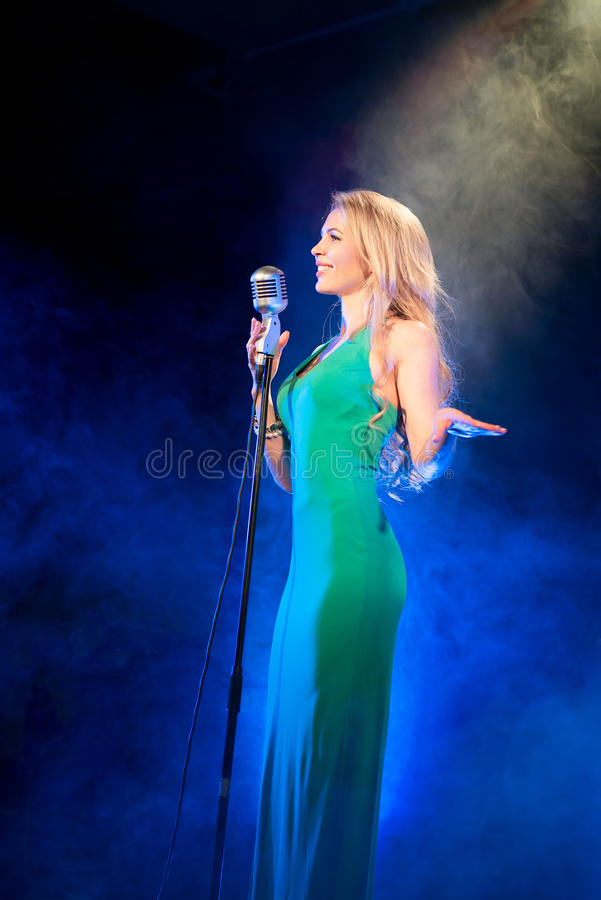 Singer woman singer sings a song with retro microphone on blue smoke background. Concert. Singer woman singer sings a song with retro microphone on blue smoke stock images