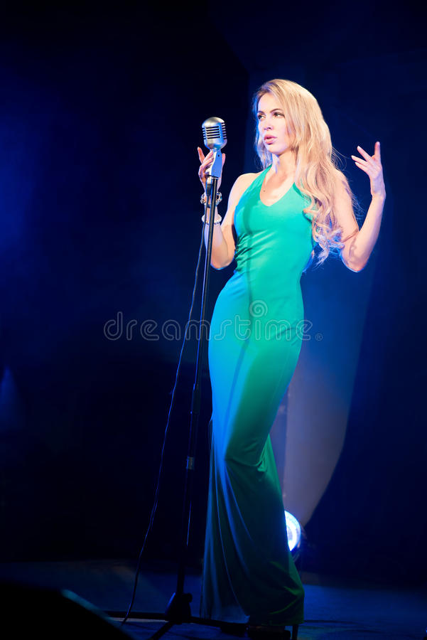 Singer woman singer sings a song with retro microphone on blue smoke background. Concert. Singer woman singer sings a song with retro microphone on blue smoke stock photo