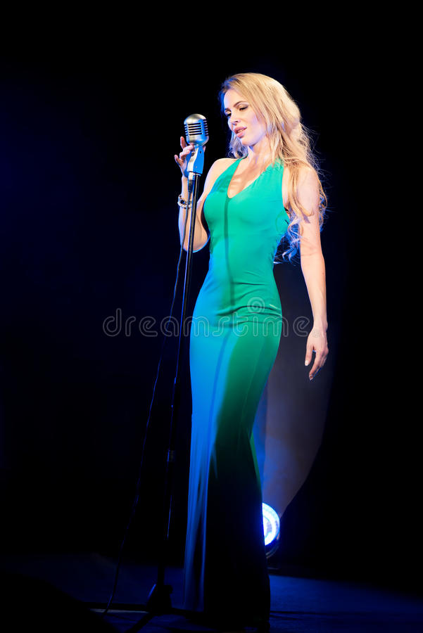 Singer woman singer sings a song with retro microphone on blue smoke background. Concert. Singer woman singer sings a song with retro microphone on blue smoke stock photos