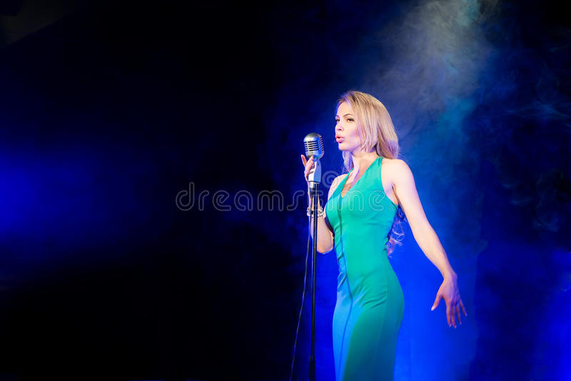 Singer woman singer sings a song with retro microphone on smoke background. Singer woman singer sings a song stock photo