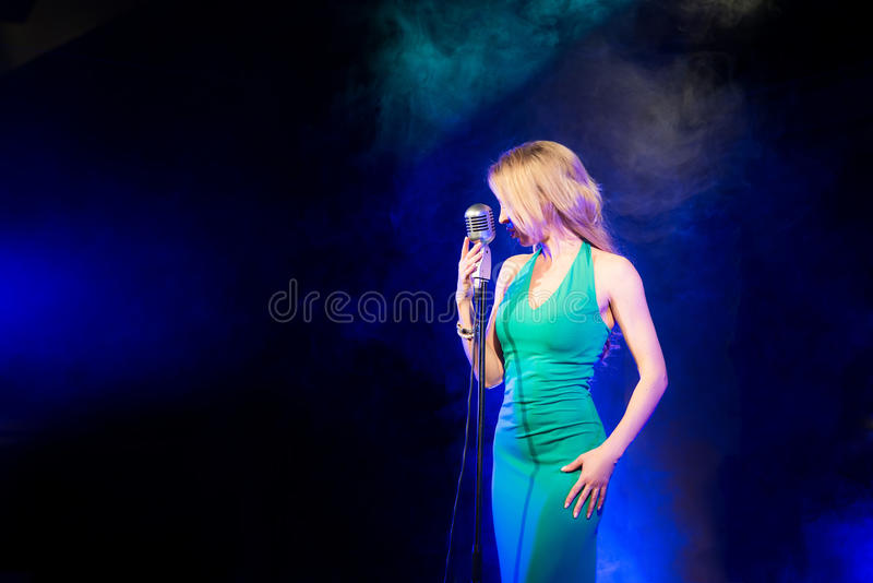 Singer woman singer sings a song with retro microphone on smoke background. Singer woman singer sings a song royalty free stock photos