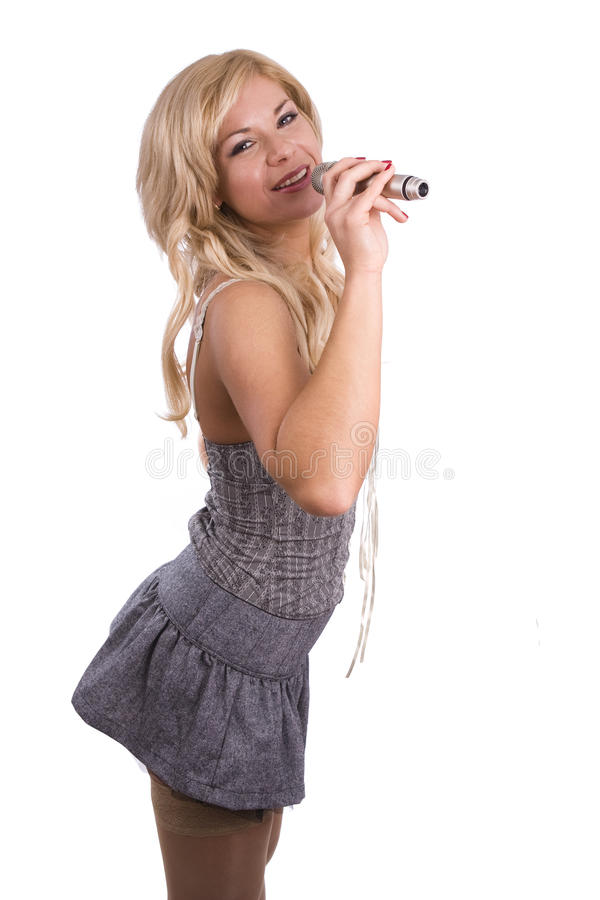 Singer. Young girl singing into microphone. Pretty girl singing into microphone. Young female singer with blond hair singing a song. Woman laying down some royalty free stock photo