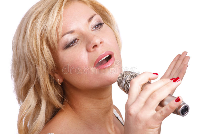 Singer. Young girl singing into microphone. Pretty girl singing into microphone. Young female singer with blond hair singing a song. Woman laying down some stock image