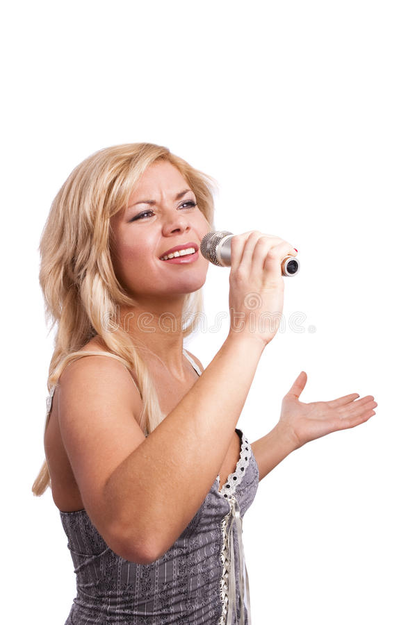 Singer. Young girl singing into microphone. Pretty girl singing into microphone. Young female singer with blond hair singing a song. Woman laying down some royalty free stock photos