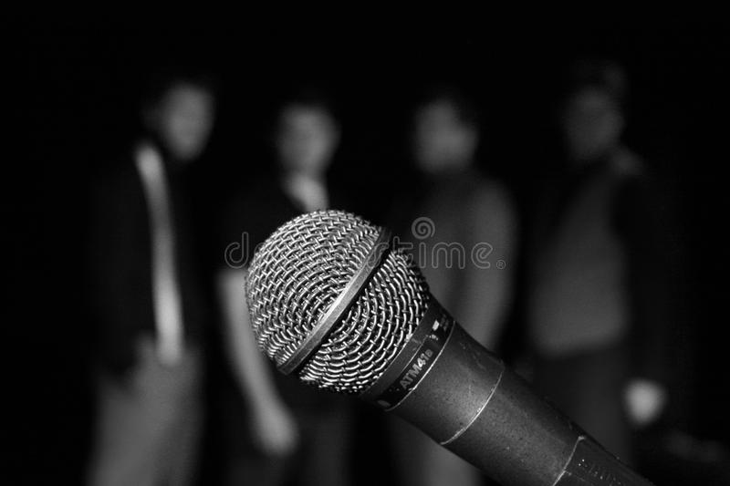 Singers behind a mic. 4 singers out of focus behind a microphone stock images