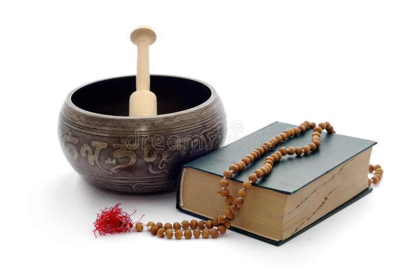Singing bowl, book and wooden rosary. stock image