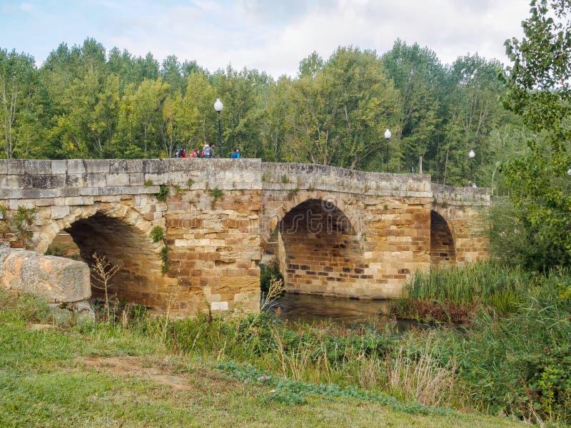 Singing Bridge - Sahagun. Camino pilgrims walk on the Singing Bridge (Puente Canto), an 11th century stone arched bridge, over the Cea River - Sahagun royalty free stock image