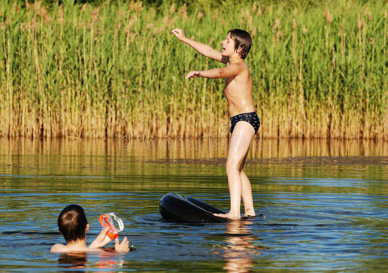 Singing And Conducting. The boy standing on a tube and keeps on singing and conducting in a middle of the lake stock images