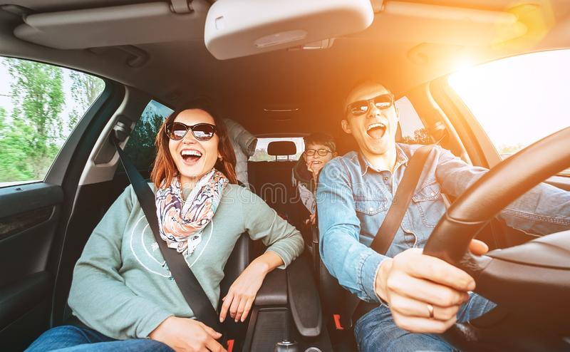 Cheerful young traditional family has a long auto journey and singing aloud the favorite song together. Safety riding car concept royalty free stock photography
