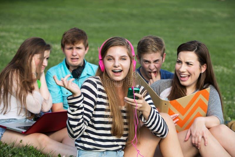 Singing Girl Annoying Friends. Singing teenage girl annoying friends studying outdoors stock images