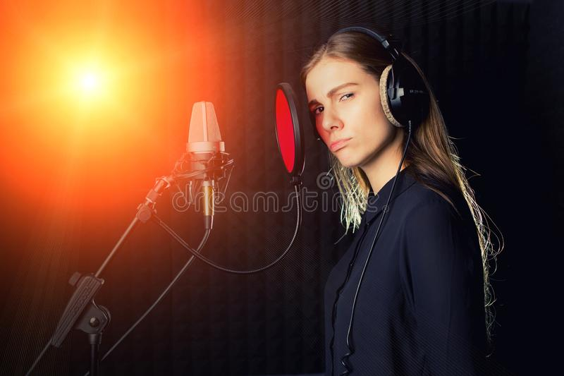 Singing girl sing to the professional microphone in the record studio. Process of create a new hit song by young singer.  royalty free stock photo