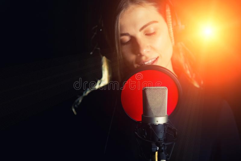 Singing girl sing to the professional microphone in the record studio. Process of create a new hit song by young singer.  royalty free stock images