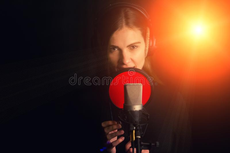 Singing girl sing to the professional microphone in the record studio. Process of create a new hit song by young singer.  royalty free stock image