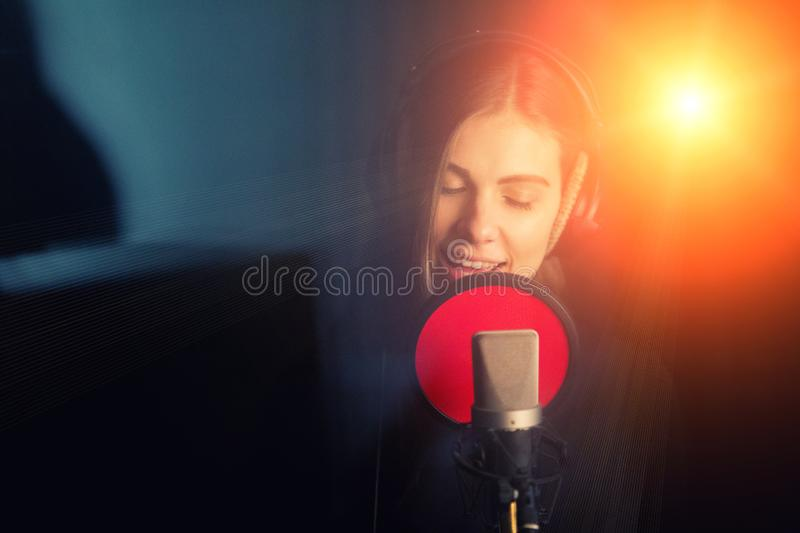 Singing girl sing to the professional microphone in the record studio. Process of create a new hit song by young singer.  stock image