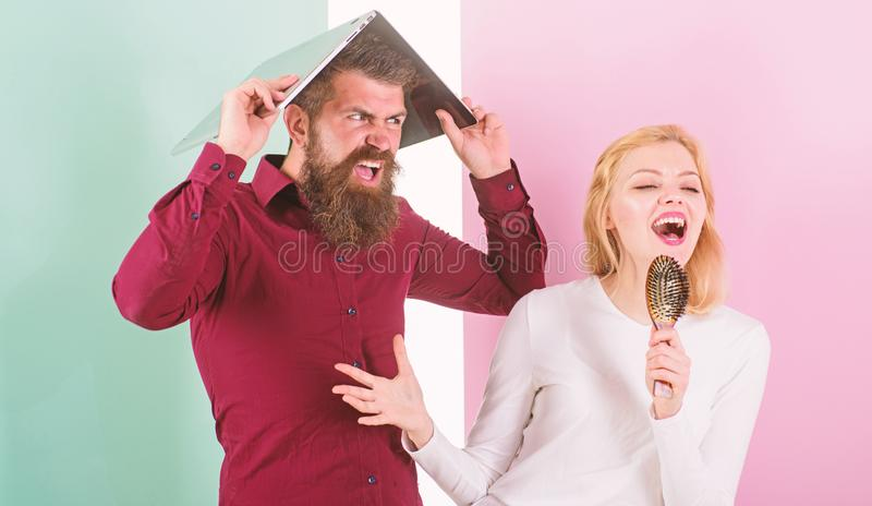 Singing is her passion. Lady sing using hair brush as microphone while man annoyed hiding under laptop. Better sing at royalty free stock images