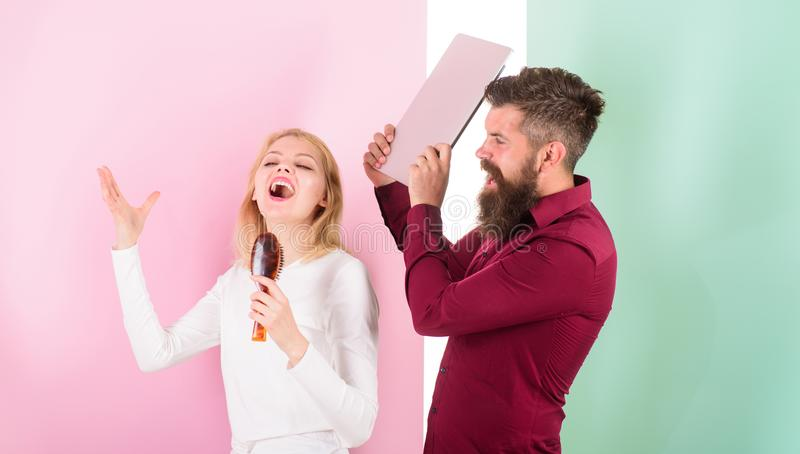 Singing is her passion. Lady sing using hair brush as microphone while man annoyed going beat her laptop. Better sing at stock photography