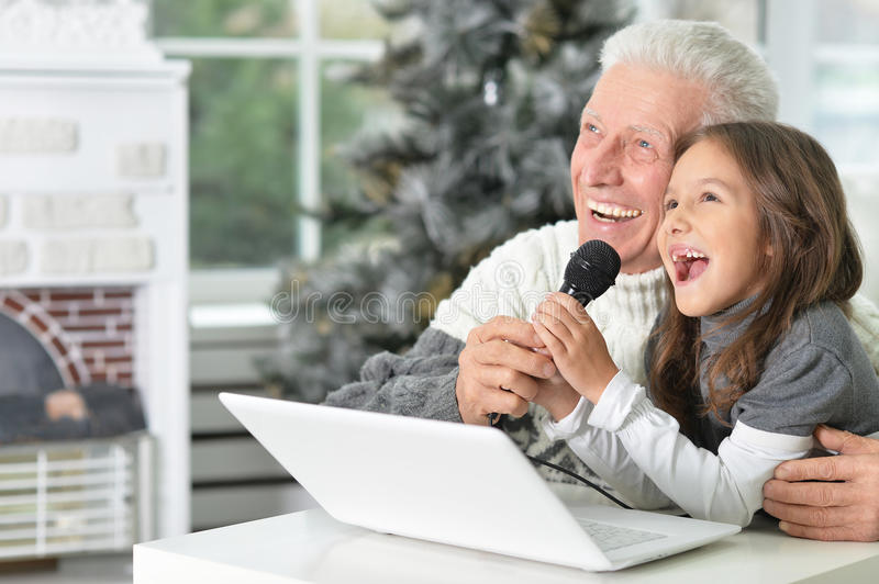Singing karaoke at home. Happy grandfather and his granddaughter singing karaoke at home royalty free stock image