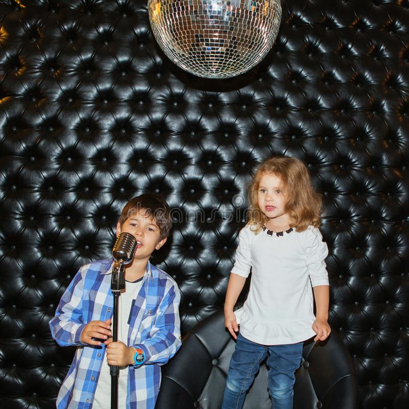 Singing little children with a microphone on a rack. Against a black wall royalty free stock image