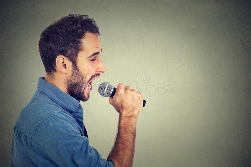 Singing man. On gray wall background stock photos
