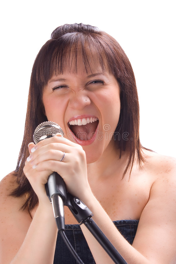 Singing with a mic. Girl singing with a mic isolated in white background stock photography
