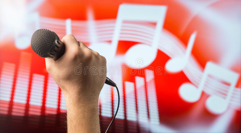 Singing microphone in hand stock photography