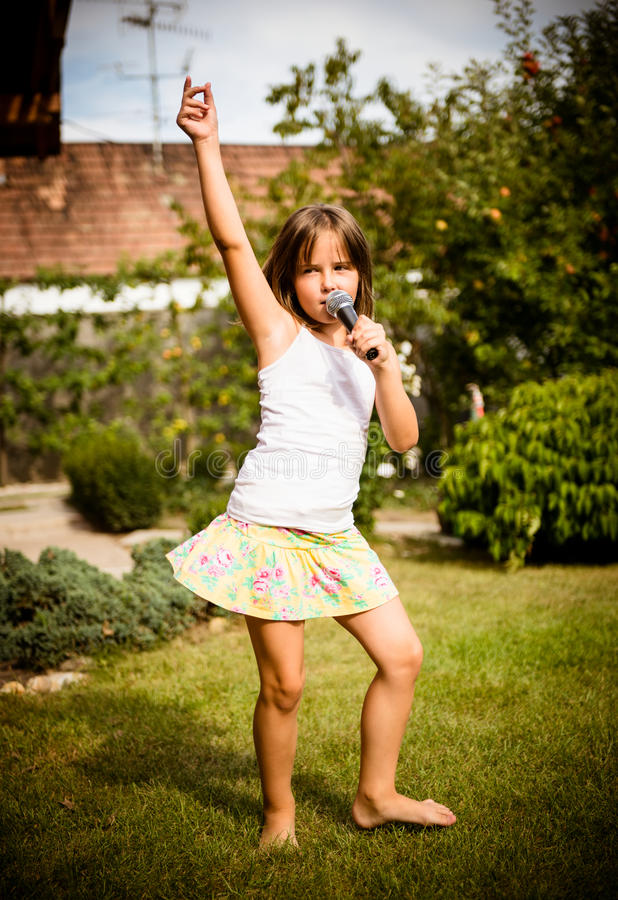 Singing is my joy. Happy childhood - child singing with microphone outdoor in backyard stock photos