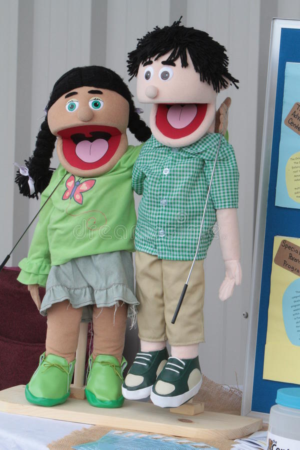 Singing Puppets. Happy boy and girl puppets with mouths wide open as if in song stock image