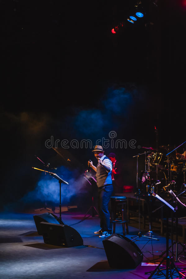 Singing on stage in dark studio. Peter Ong and Friends Concert at the Kuala Lumpur Performing Arts Centre stock photography