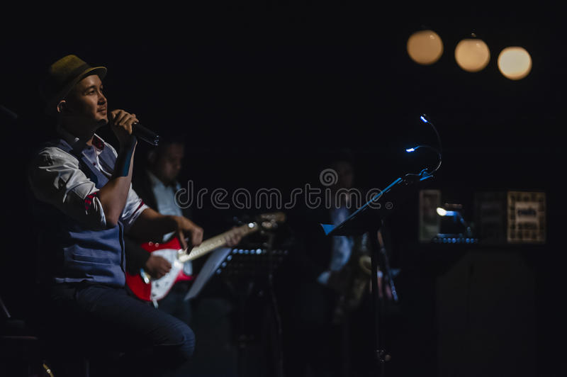 Singing on stage in dark studio. Peter Ong and Friends Concert at the Kuala Lumpur Performing Arts Centre royalty free stock photo