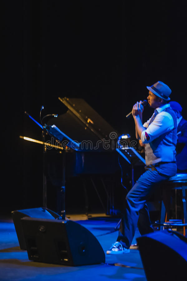 Singing on stage in dark studio. Peter Ong and Friends Concert at the Kuala Lumpur Performing Arts Centre stock photos