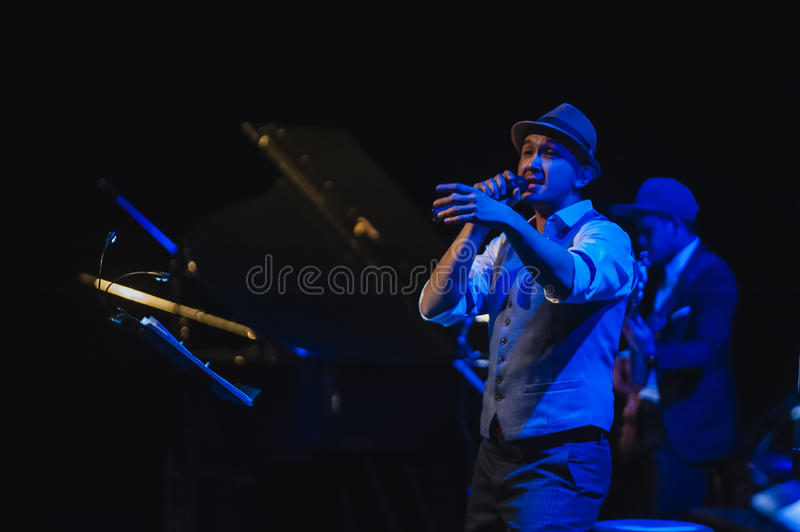 Singing on stage in dark studio. Peter Ong and Friends Concert at the Kuala Lumpur Performing Arts Centre royalty free stock image