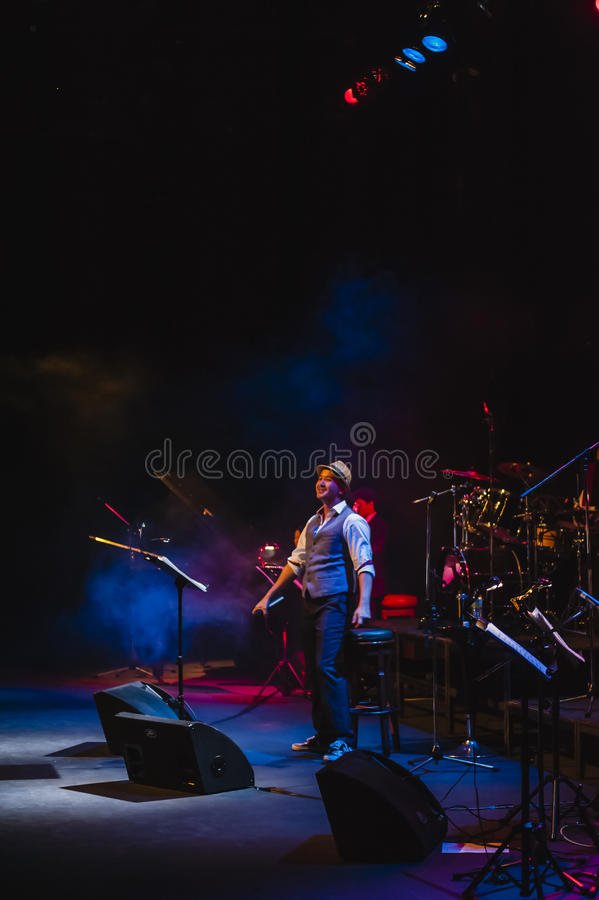 Singing on stage in dark studio. Peter Ong and Friends Concert at the Kuala Lumpur Performing Arts Centre stock photo