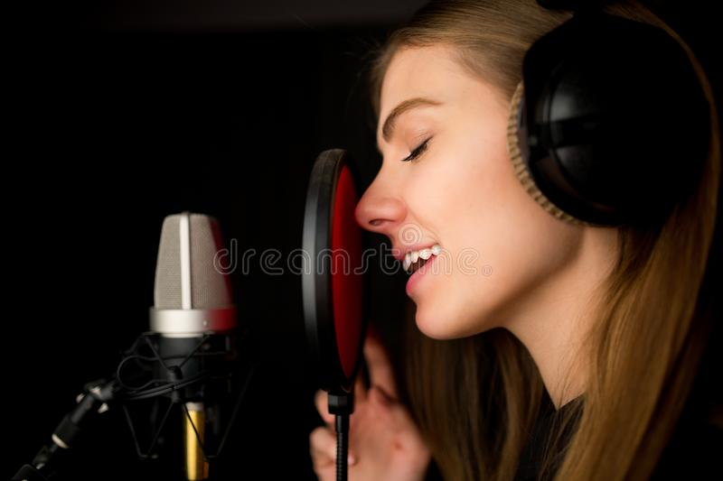 Singing young girl in recording studio. royalty free stock photos