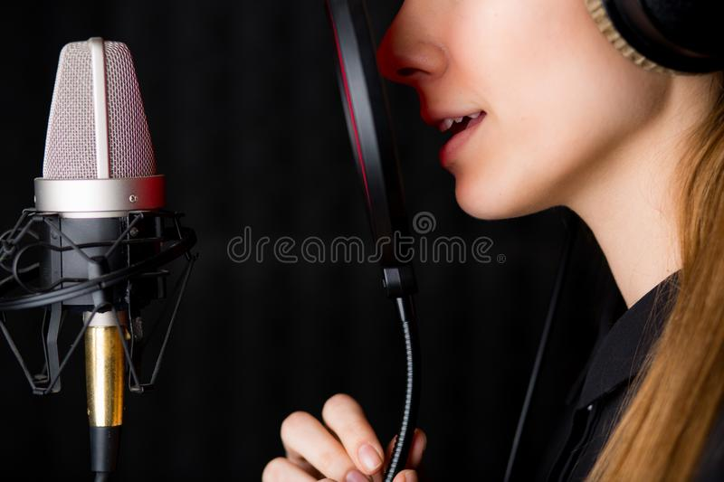 Singing young girl in recording studio. stock photo