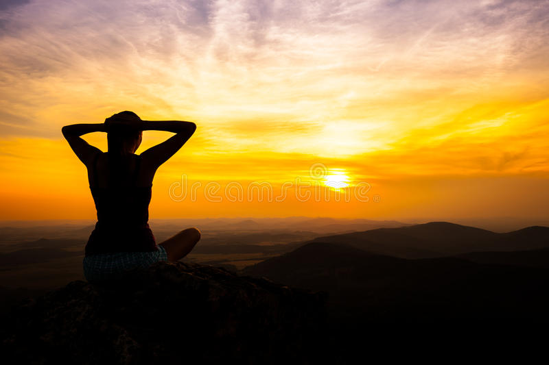 Single adult woman silhouette on rock stock photography