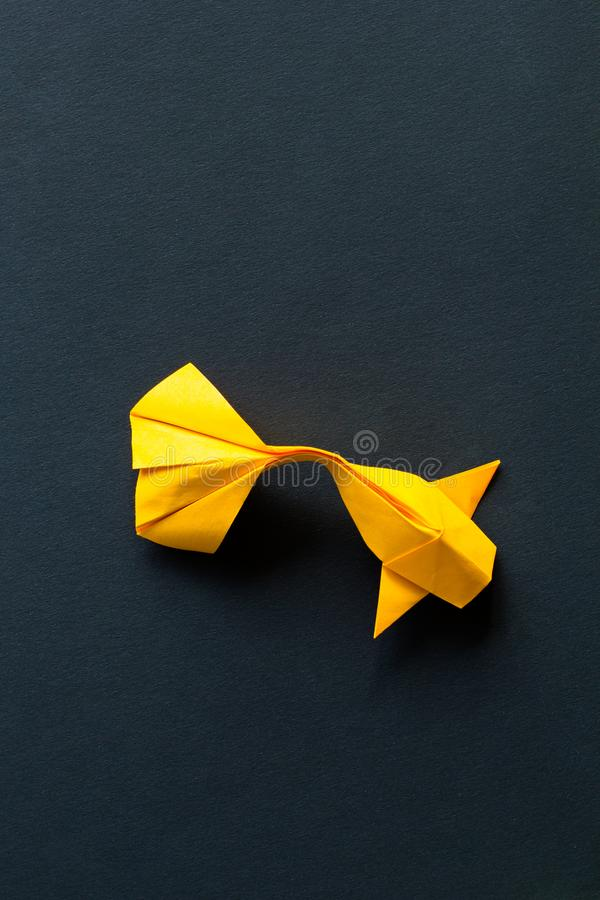 Single alone handmade paper craft origami gold or yellow koi carp fish on black background.Top view, centeral plece stock photo