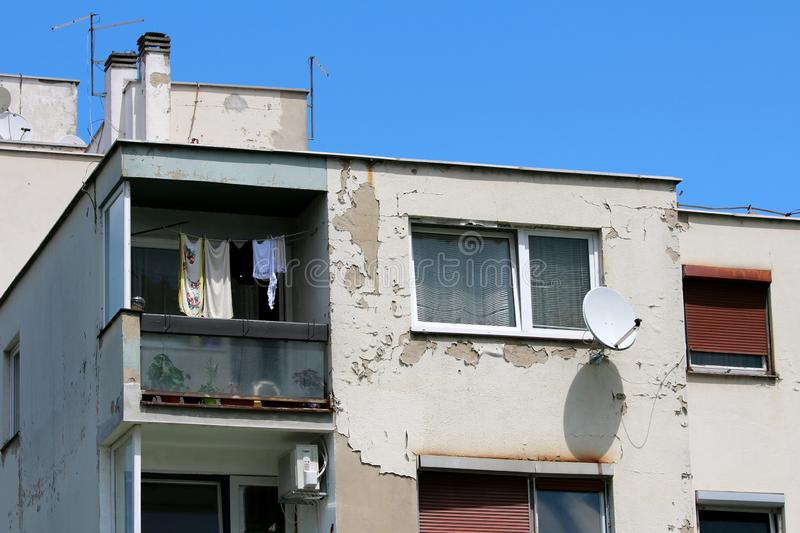 Single apartment with windows and open balcony surrounded with dilapidated cracked old facade and other apartments on clear blue. Sky background stock photos