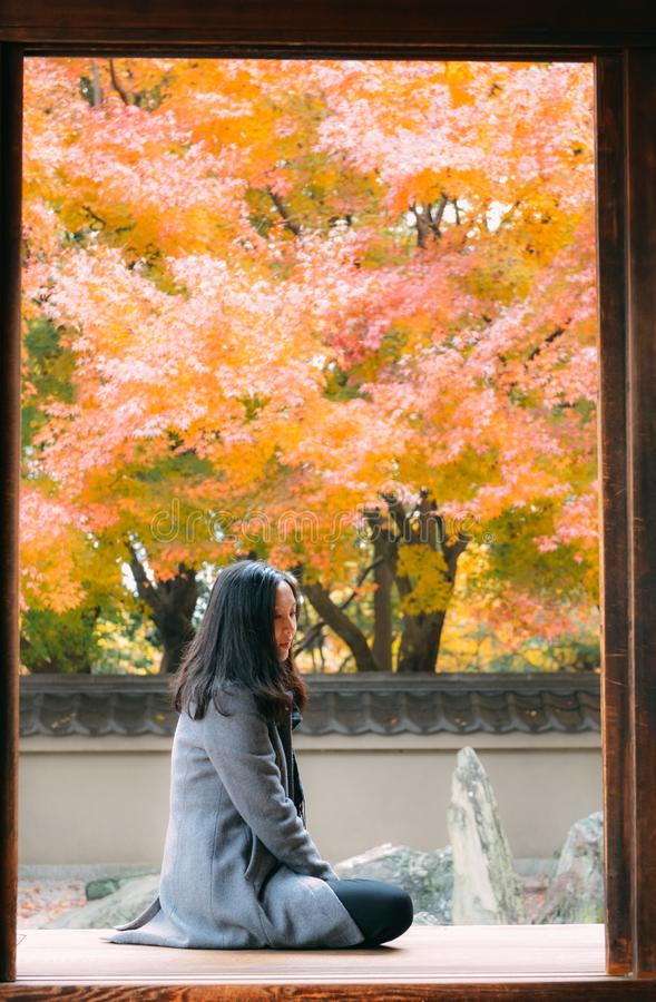 Girl looking at red maple trees in Japanese temple, Kyotogirl enjoying autumn foliage in Japanese temple, Kyoto royalty free stock photography