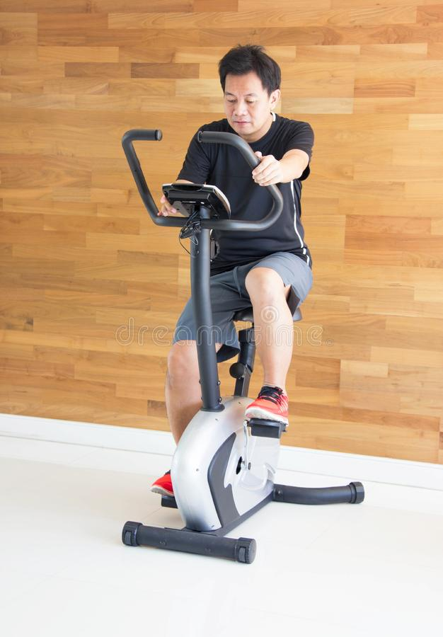 Single Asian Man On Excercise Bike At Fitness Center. royalty free stock photo