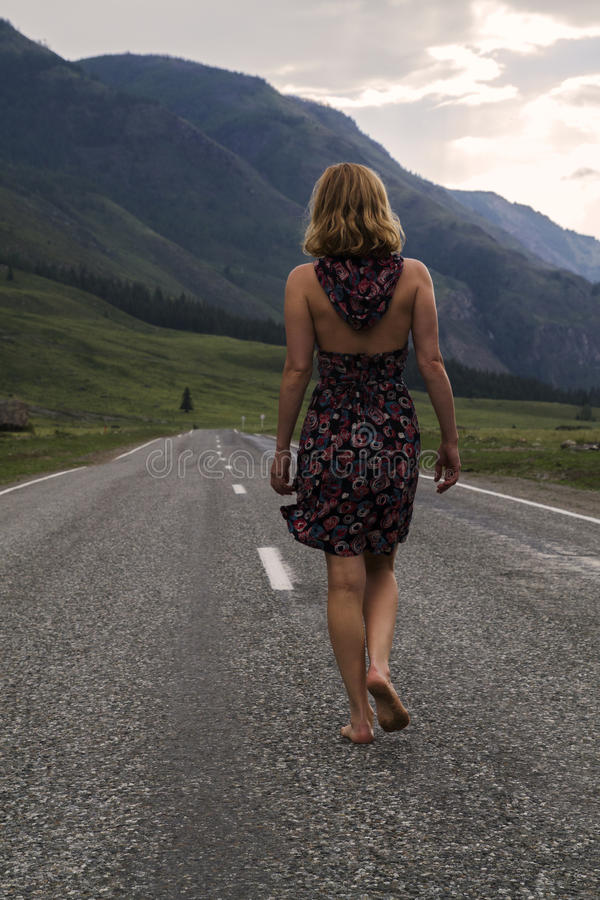 Single barefoot woman is walking along the mountain road. Travel, tourism and people concept stock photography