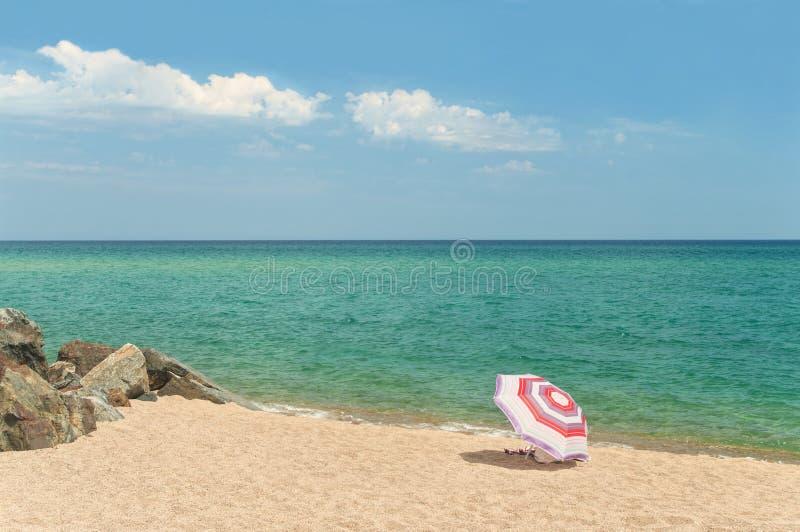 Single beach umbrella on empty beach with rocks royalty free stock photography