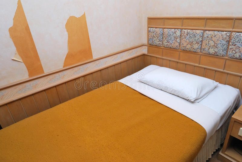 Single bed in old hotel room stock images
