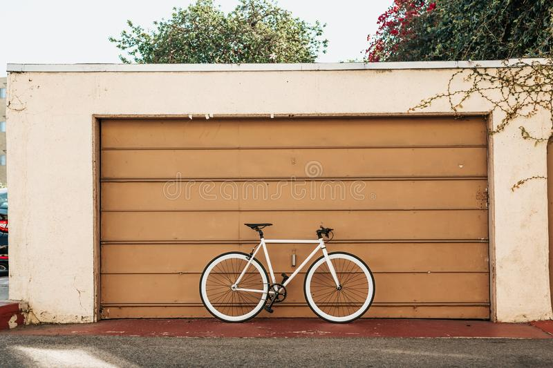 Single bicycle parked near a large brown garage on a sunny day. A single bicycle parked near a large brown garage on a sunny day royalty free stock image