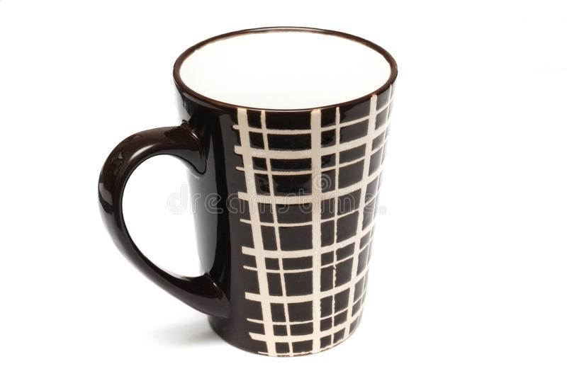 A single big tall dark brown coffee cups with simple lines design. A photo taken on a single big tall dark brown coffee cups with simple lines design against a stock image