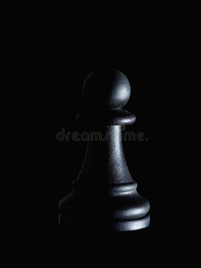 Single black chess piece pawn on black, dramatic lighting. Manipulation, powerlessness, hidden victim concept. Single black chess piece pawn on black, dramatic royalty free stock photo